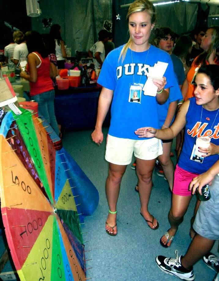 "SPECTRUM/Kaitlin Kisling and Christine Russo test their luck at the ""winning wheel"" at the June 19, 2010 New Milford High School grad party. Photo: Norm Cummings / The News-Times"