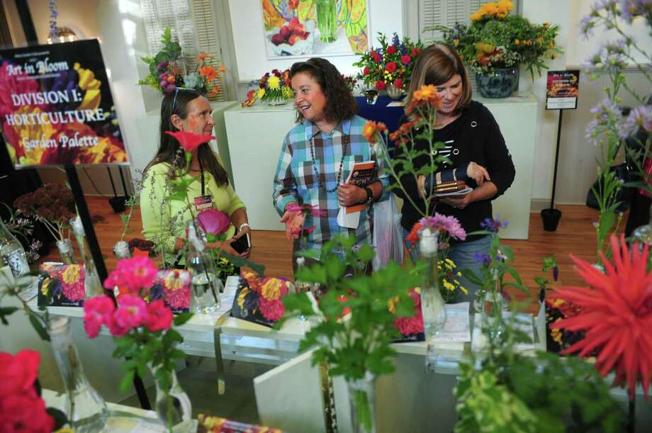 Wilton Garden Club member Sandi Blaze, left, introduces the National Garden Club Standard Flower Show, Art in Bloom, to visitors Friday, October 13, 2017, at Old Town Hall in Wilton Conn. Art in Bloom features 28 luscious flower designs inspired by fine art art and sculpture and hundreds of horticulture specimens. The show opened on Friday, and will continue on Saturday, October 14, from 10 a.m. to 4 p.m. Tickets at the door are $10. Students under 18 can come in free. Photo: Erik Trautmann / Hearst Connecticut Media / Norwalk Hour