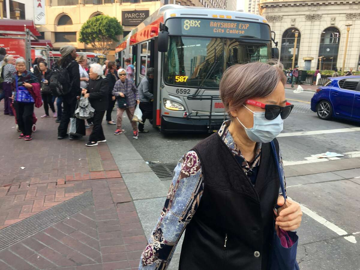 A woman wears a respirator mask on Market St. in San Francisco on Friday, Oct. 13, 2017.