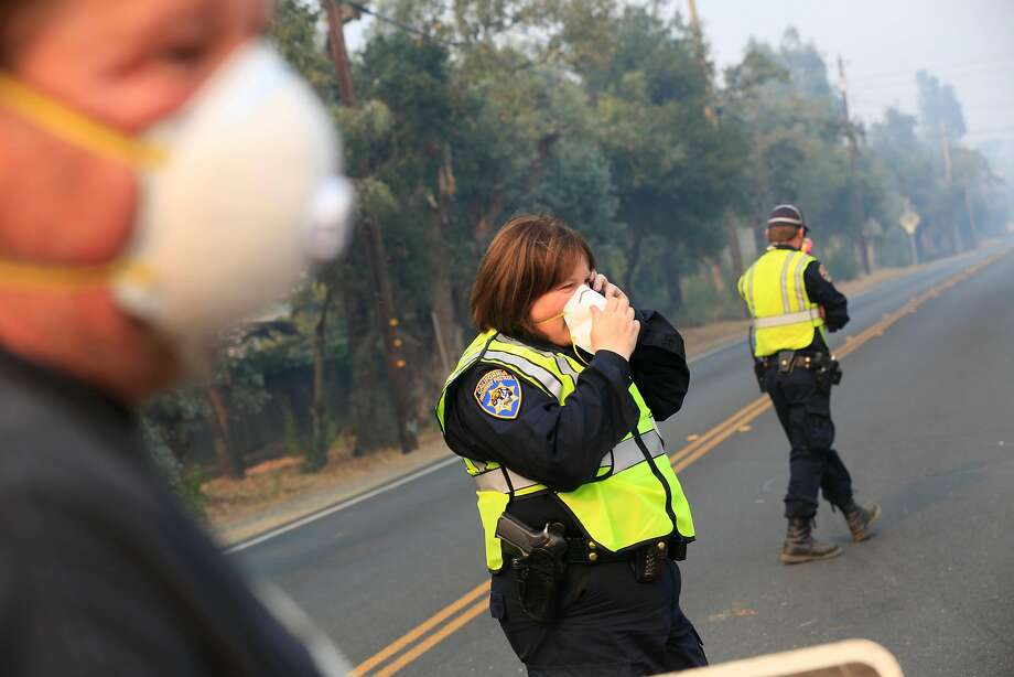 California Highway Patrol officer Tracy Ross (center) talks on the phone while assiting Tom Sours (left)  of Napa, as he was trying to get to his home to pick up some items on Friday, October 13, 2017 in Napa, Calif. Photo: Lea Suzuki, The Chronicle
