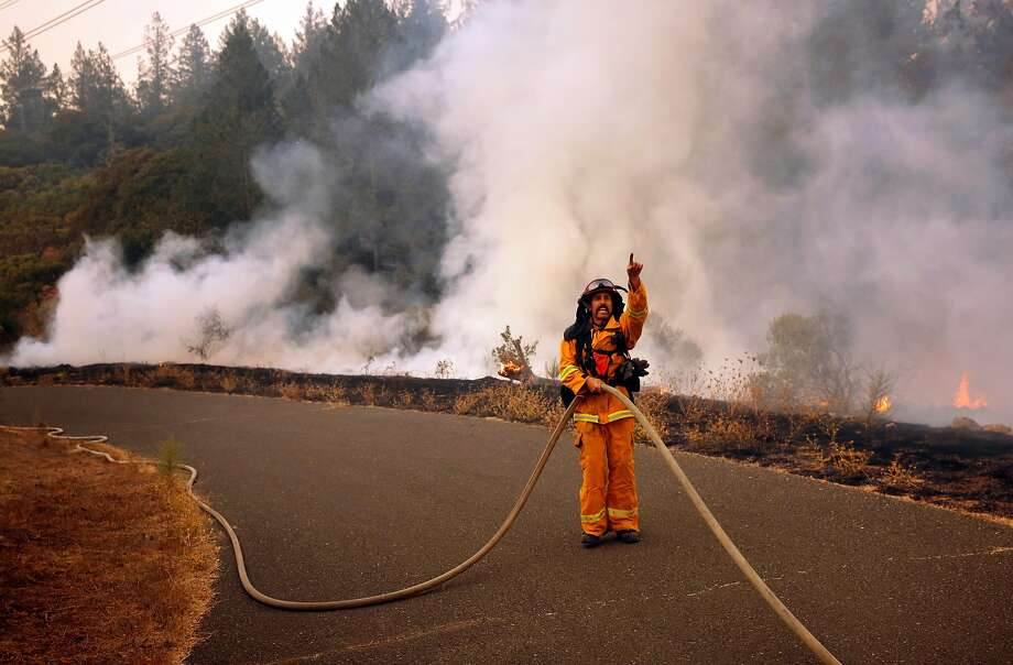 Captain Mike Harrison of Santa Rosa Fire directs his team of firefighters in containing a small roadside fire in the Oakmont neighborhood of Santa Rosa. Amid an evacuation order, homes remained unburned. Photo: Michael Macor, The Chronicle