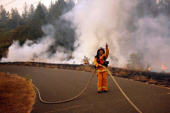 Captain Mike Harrison of Santa rosa fire directs his team of firefighters in containing a small roadside fire in the Oakmont neighborhood of Santa Rosa, Ca. on Tuesday October 10, 2017. Massive wildfires ripped through Napa and Sonoma counties, destroying hundreds of homes and businesses on Monday morning.