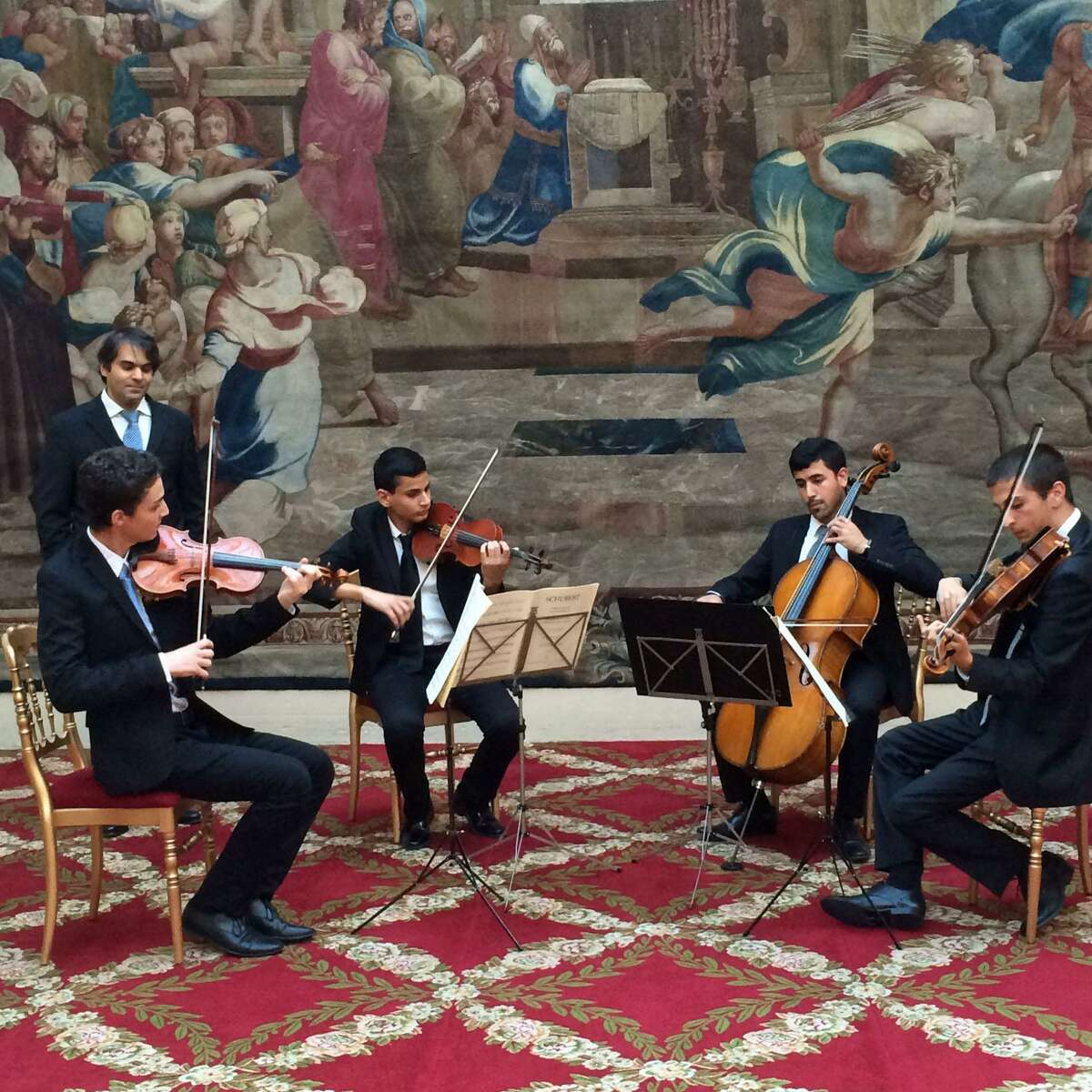 Above, a Polyphony quartet, with Nabeel Abboud-Ashkar in the background, playing at a Climate Change reception dinner at the Élysée Palace. Below, Polyphony string musicians with their instruments.