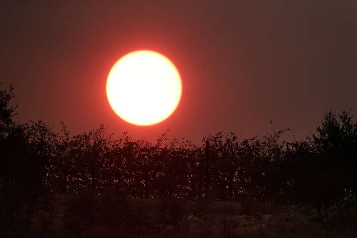 The sun, turned red from smoke in the area, sets behind a vineyard on Lovall Valley Road as the Partrick Fire continue to burn slowly east of Sonoma, Calif., on Thursday, October 12, 2017. The Napa and Sonoma valleys continue to be under threat from several fires not yet under control and growing fears that strong winds might worsen the situation.