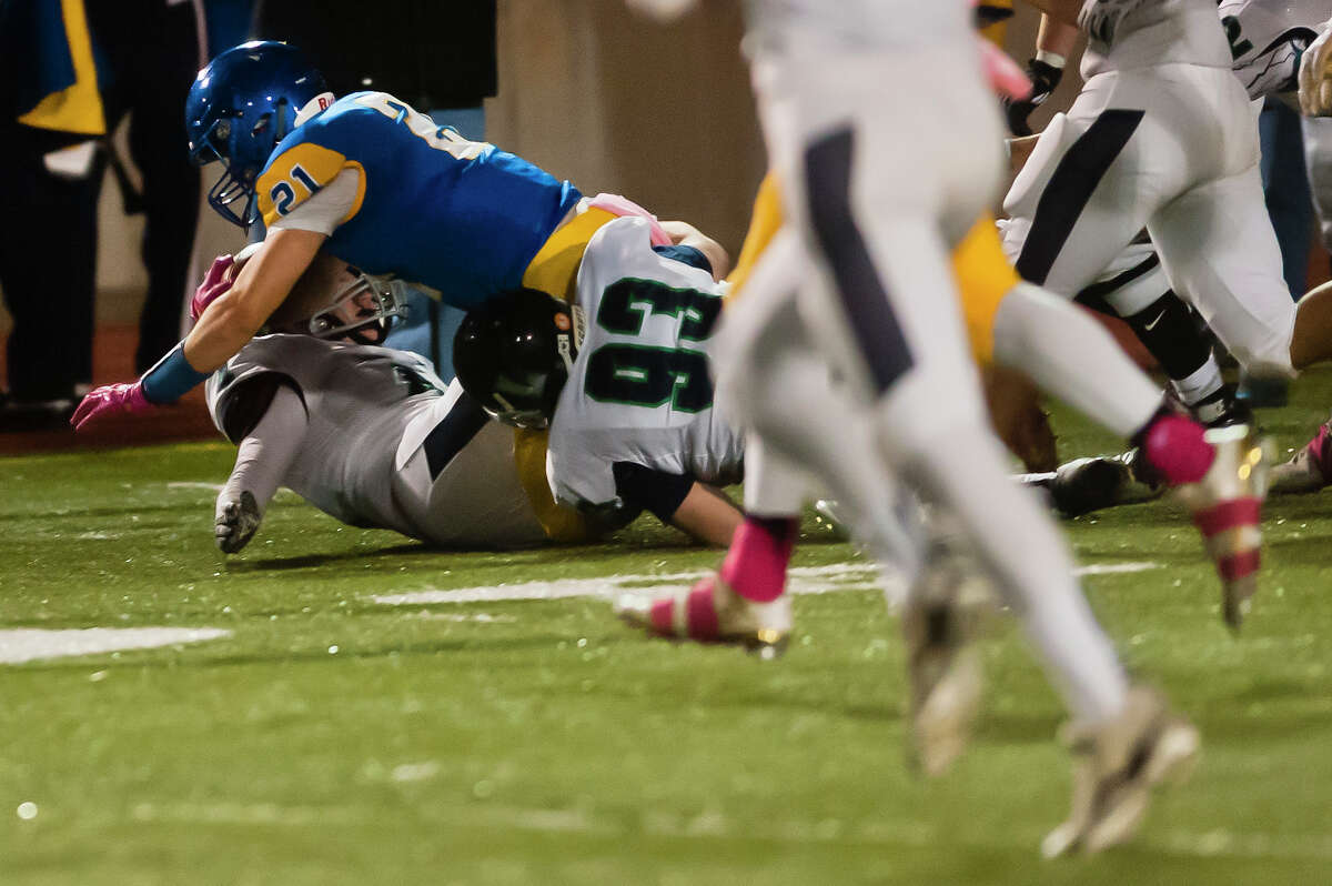 Midland senior Martin Money dives forward as he is tackled by Lapeer players during their game on Friday, Oct. 13, 2017 at Midland Community Stadium. (Katy Kildee/kkildee@mdn.net)