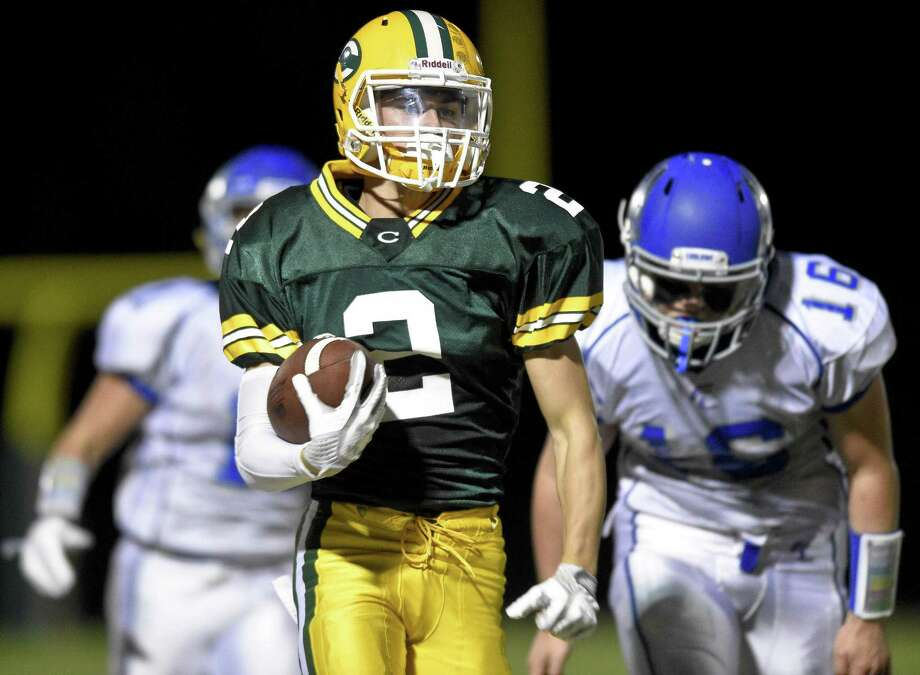 Trinity Catholic's John Petrizzi carries the ball past Fairfield Ludlowe defenders on his way to a third-quarter touchdown in a FCIAC game at Gaglio Field on Friday in Stamford. Trinity defeated Ludlowe 40-19. Photo: Matthew Brown / Hearst Connecticut Media / Stamford Advocate