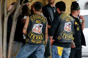 FILE - In this May 17, 2015 file photo, bikers congregate against a wall while authorities investigate a Twin Peaks restaurant in Waco, Texas, after gunfire erupted between rival biker gangs - Bandidos and Cossacks - at the restaurant.  Law enforcement did nothing on the day to stop a meeting in Waco  in 2015 that erupted into the deadliest shootout between biker gangs in U.S. history, even though they had detailed advance intelligence that the encounter between the Cossacks and Bandidos was likely to turn violent. That finding came from a review by The Associated Press of a trove of evidence compiled by prosecutors for use in state trials of 154 bikers, with the first trial slated to begin this week of Oct. 11, 2017. (Rod Aydelotte/Waco Tribune-Herald via AP, File)