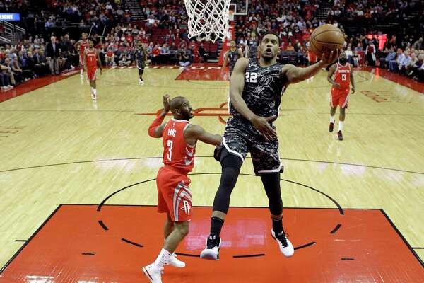 Houston Rockets forward P.J. Tucker, left, is guarded by San Antonio Spurs guard Tony Parker (9) in the first half of an NBA basketball game Friday, Dec. 15, 2017, in Houston. (AP Photo/George Bridges)