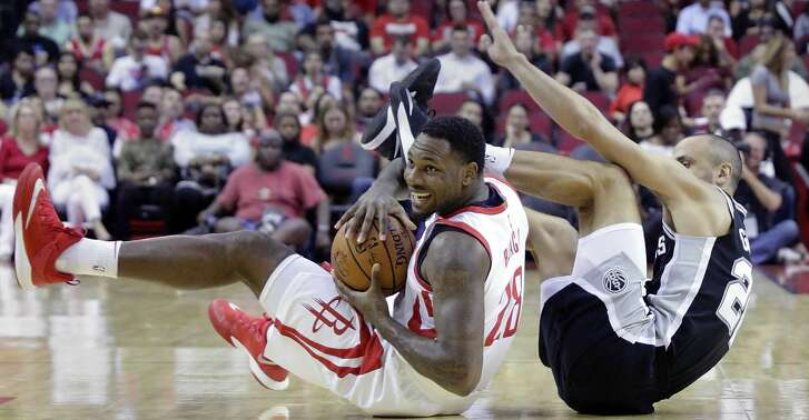 Houston Rockets forward Tarik Black (28) comes up with control of a loose ball against San Antonio Spurs guard Manu Ginobili (20) in the first half of an NBA preseason basketball game Friday, Oct. 13, 2017, in Houston. (AP Photo/Michael Wyke)