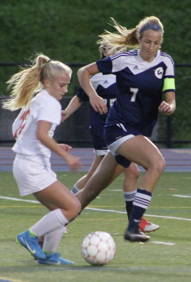 Danbury's Alexis Estanqueiro, left, moves the ball upfield as Wilton's Chloe Zimmermann defends during the girls soccer game at Danbury High School Oct. 13, 2017. Photo: Richard Gregory / Richard Gregory