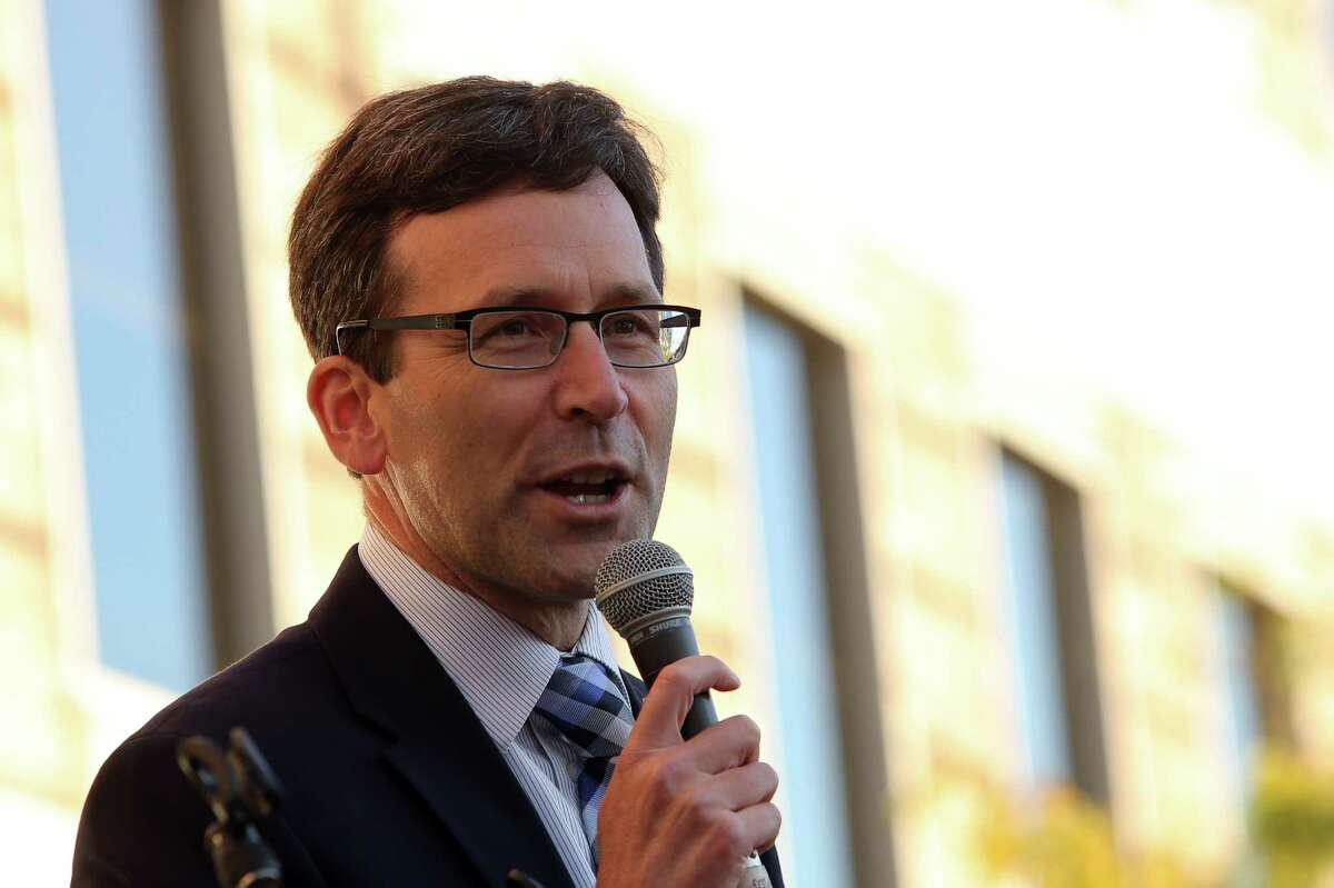 Washington Attorney General Bob Ferguson speaks to crowds outside of the Hyatt Regency Bellevue during a protest against the policies of Secretary of Education Betsy DeVos who spoke at the Washington Policy Center's annual gala, Friday evening, Oct. 13, 2017.