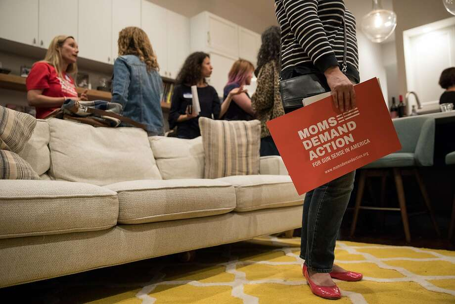 A woman holds a sign supporting Moms Demand Action for Gun Sense in America at a meeting in a Glen Park home in S.F. Photo: Erin Lubin, Special To The Chronicle