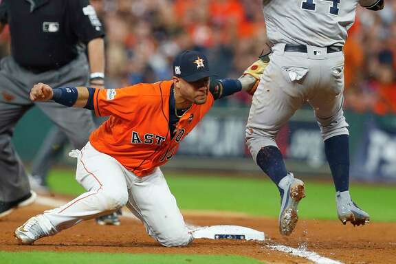The Astros' Yuli Gurriel tags out Yankees second baseman Starlin Castro on a throw that pulled Gurriel off first base.