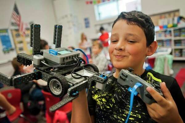 Alex Posch of Midland, 9, shows off a robot he is experimenting with along with his Central Park Elementary classmates on Friday. Donors to the school, which has a STEM focus, were able to tour the facility and observe classrooms during an open house event that took place Friday morning. (Katy Kildee/kkildee@mdn.net)