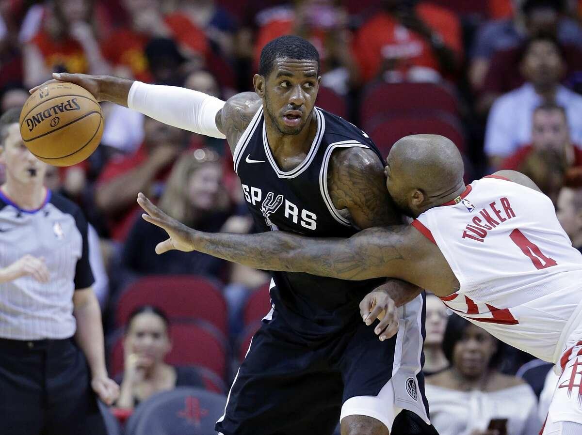 San Antonio Spurs forward LaMarcus Aldridge (12) looks to drive around Houston Rockets forward PJ Tucker (4) in the first half of an NBA preseason basketball game Friday, Oct. 13, 2017, in Houston. (AP Photo/Michael Wyke)