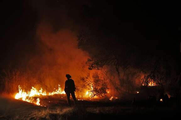 A firefighers keeps an eye on a flare up on Lovall Valley Road as crews continue to monitor several wildfires near Sonoma, Calif., on Friday, October 13, 2017. Emergency personnel were deployed to the perimeter of several fires as the threat of gusting winds had them worried that the fires would grow overnight.