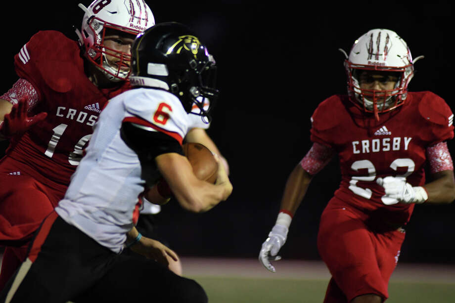 Crosby junior linebacker Hunter Moore, left, targets Caney Creek junior quarterback Cody Fay (6) with backup from teammate Zachary Simon (23) on a running play in the 1st quarter of their District 21-5A matchup at Cougar Stadium in Crosby on Oct. 13, 2017. (Photo by Jerry Baker/Freelance) Photo: Jerry Baker, Freelance / Freelance