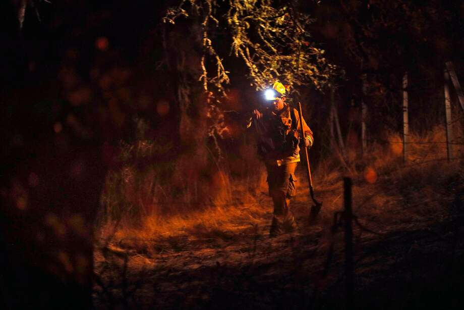 A firefighter walks through brush while looking for flare ups outside Robert Louis Stevenson Park near Calistoga, Calif., on Saturday, October 14, 2017. Emergency personnel were deployed to the perimeter of several fires as the threat of gusting winds had them worried that the fires would grow overnight. Photo: Carlos Avila Gonzalez, The Chronicle
