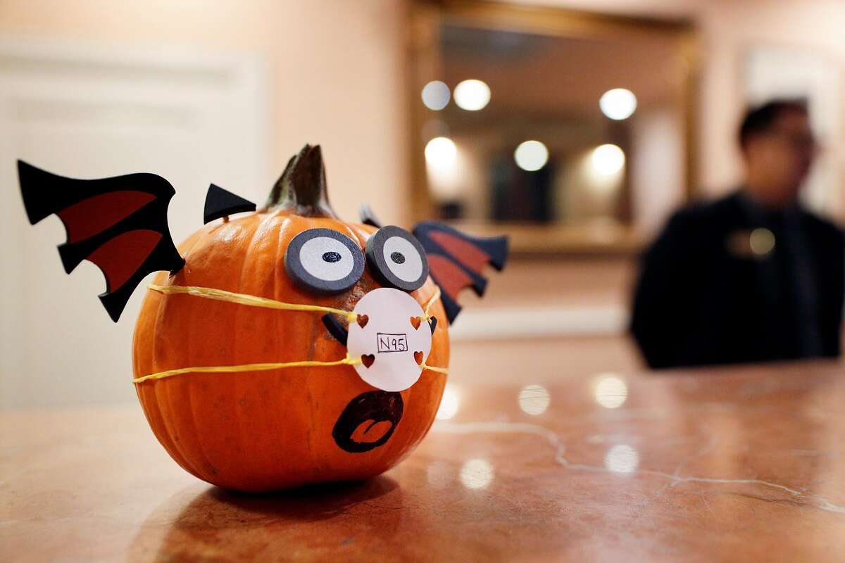 A decorative Halloween pumpkin sports a makeshift face mask at the reception desk at the Napa River Inn in Napa, Calif., on Friday, October 13, 2017. The Napa River Inn, which is privately owned and has 66 rooms, is staying open to offer free housing to evacuees and first responders. It's operating with a limited staff because many employees lost homes.