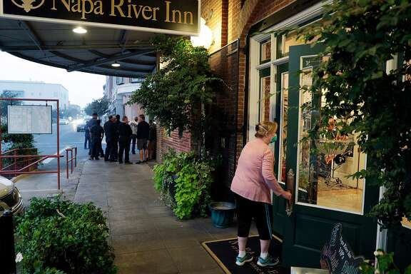 Mel Hullana, a resident of Napa who was evacuated due to the wildfires Monday, enters the Napa River Inn in Napa, Calif., on Friday, October 13, 2017. The Napa River Inn, which is privately owned and has 66 rooms, is staying open to offer free housing to evacuees and first responders.  It's operating with a limited staff because many employees lost homes.