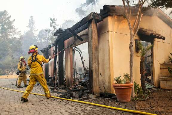 Fire fighters work on putting out hotspots and knocking down burned timber off Lovall Rd in Sonoma, California, USA 14 Oct 2017.