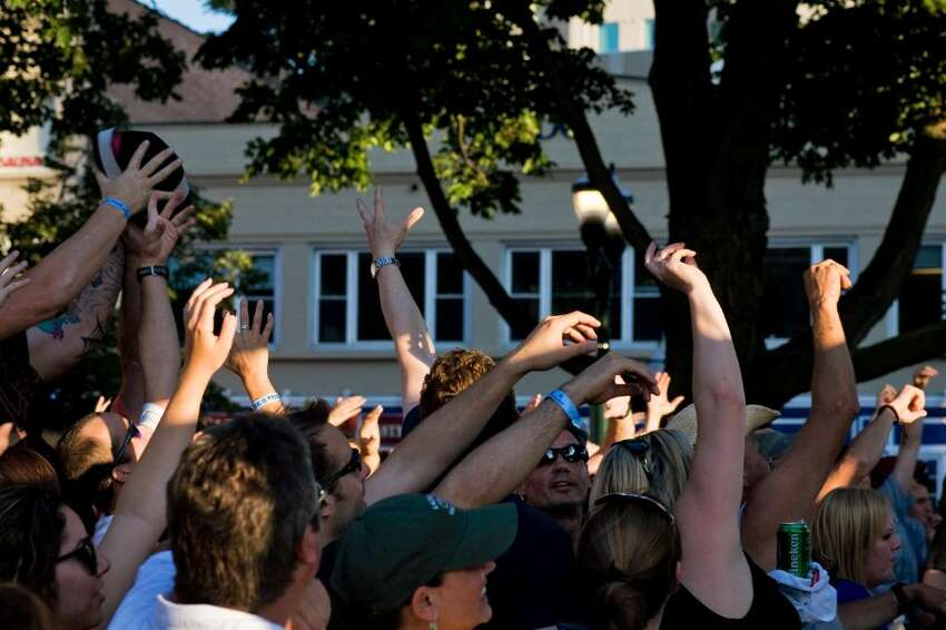 Soul Asylum and the Gin Blossoms open the Alive at Five concert series in Columbus Park in Stamford, Conn., Thursday, June 24, 2010. Here, the crowd reaches for giveaways thrown to them.
