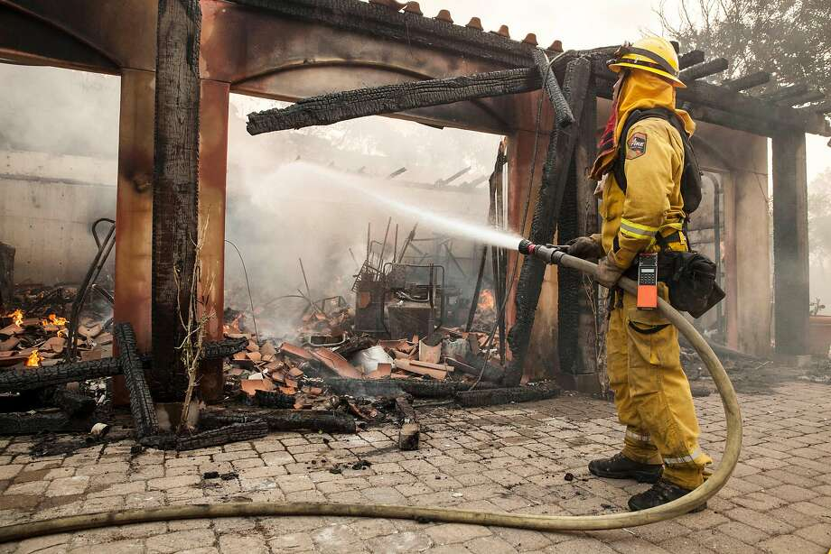 Firefighters work on putting out hot spots in a garage at a home off Lovall Road in Sonoma, Calif., on Saturday, Oct. 14, 2017. Photo: Peter DaSilva, Special To The Chronicle