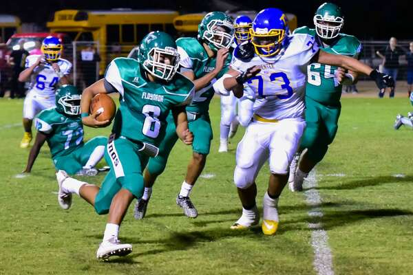 Floydada quarterback Andrew Vega, 8, turns the corner and gains yardage as Hale Center defensive lineman Quentin Bendele, 73, tires to catch him during a District 2-2A, Division I game at Floydada Friday night.