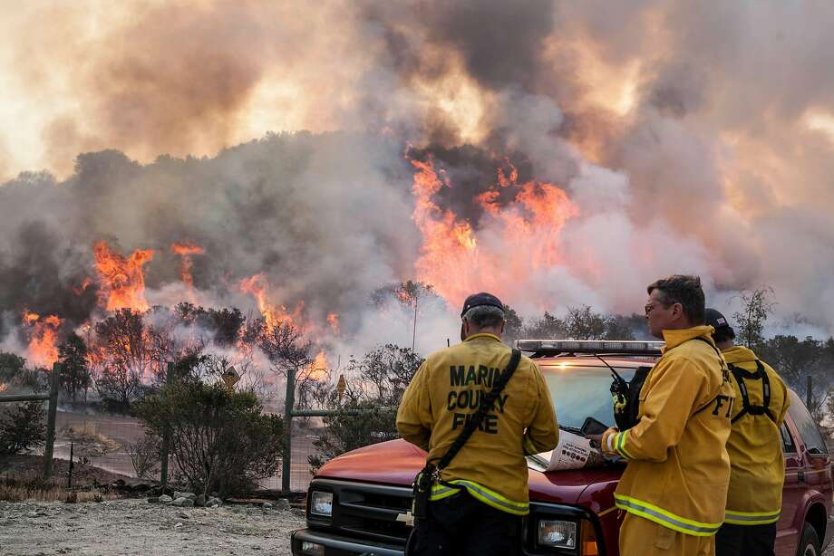 Area command fire fighters accesses a blowup through a re-burn area along Wood Vally Rd after winds kicked up flames east of Sonoma, California, USA 14 Oct 2017. Photo: Peter DaSilva, Special To The Chronicle