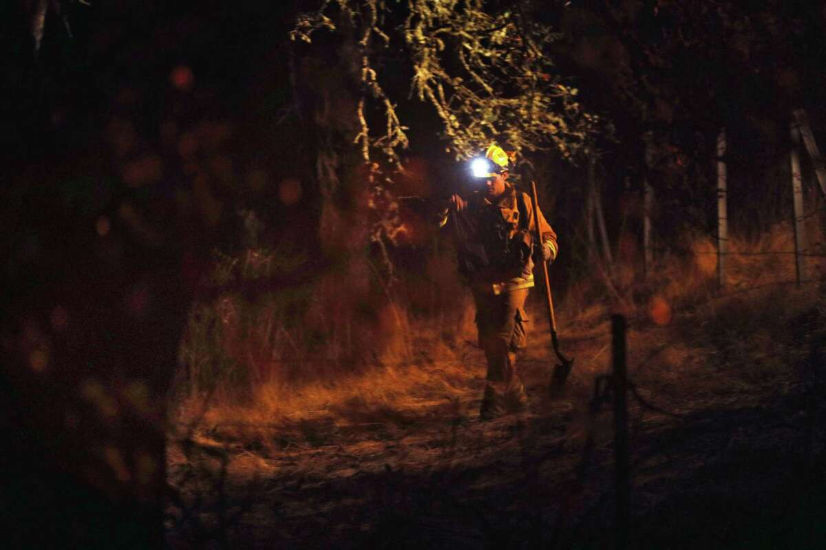 A firefighter walks through brush while looking for flare ups outside Robert Louis Stevenson Park near Calistoga, Calif., on Saturday, October 14, 2017. Emergency personnel were deployed to the perimeter of several fires as the threat of gusting winds had them worried that the fires would grow overnight.