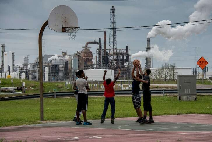 Teens play basketball at a public park near Motiva.  Many are concerned that air pollution is at the root of cancer among Port Arthur's residents.