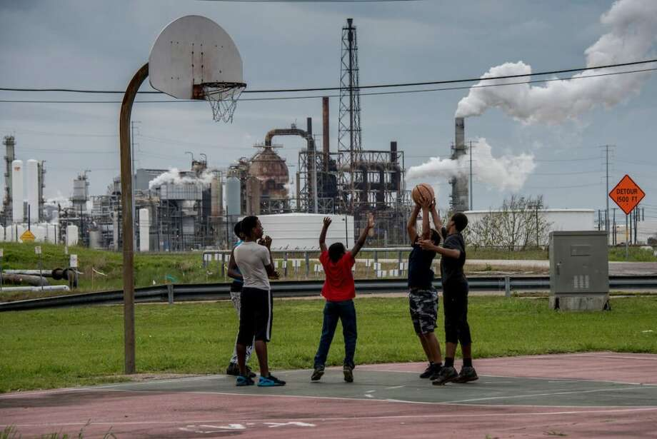 Short-term increases in air pollution can make us sick. Such pollution occurs year-round. Here: Teens play at a park near the Motiva refinery in Port Arthur.