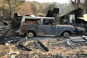 Kevin Trainor surveys the wreckage of his cousin's property on Wood Valley Road, just east of Sonoma. Trainor kept his dogs and cats at the property and restored old motorcycles in a garage there.