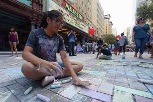 Desiree Benavides, 13, works on her art during the Artpace Chalk It Up event along Houston Street in downtown San Antonio on Saturday, Oct. 14, 2017. Local artists teamed up with the public to create chalk murals and standalone pieces on the sidewalk. Music and food added to the festive atmosphere of the event.
