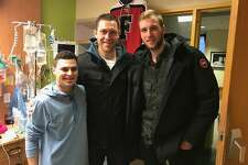 At left Charlie Capalbo is visited by Bridgeport Soundtigers Matt Carker, at center, and Loic Leduc.