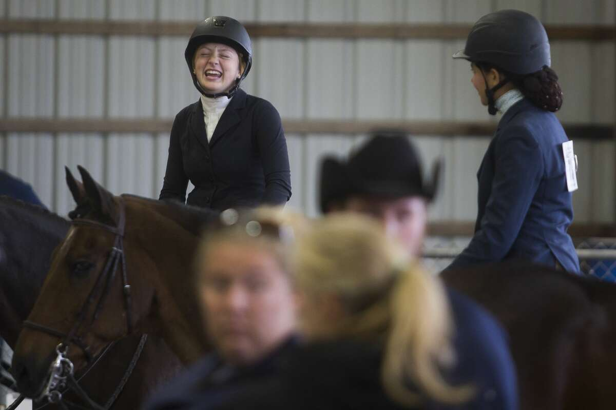 Samantha LoPresti of Ann Arbor, left, laughs as she chats with Maria Ciarelli of Milford, right, during the Michigan Interscholastic Horsemanship Association State Championship on Saturday, Oct. 14, 2017 at the Midland County Fairgrounds. (Katy Kildee/kkildee@mdn.net)