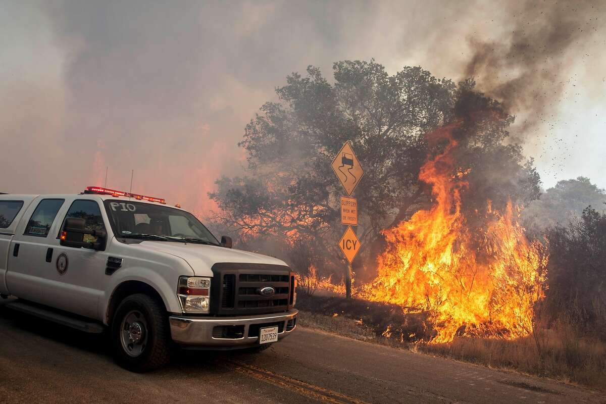Cal Fire PIO (Public Information Officer) drives passed flames along Wood Vally Rd after winds kicked up fire in a re-burn area east of Sonoma, California, USA 14 Oct 2017.