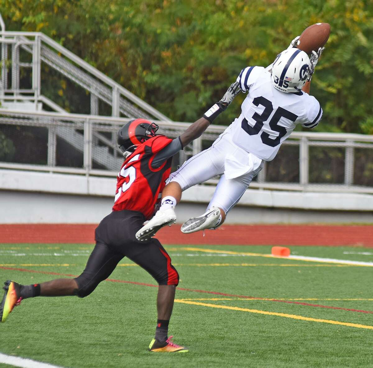 Wilton's Drew Herlyn goes airborne in an effort to make a catch as Central's Jean Desir defends Saturday.
