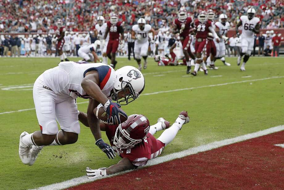 UConn's Quayvon Skanes, left, scores a second-quarter touchdown in front of Temple's Delvon Randall Saturday in Philadelphia. Photo: David Maialetti / The Philadelphia Inquirer Via AP / The Philadelphia Inquirer