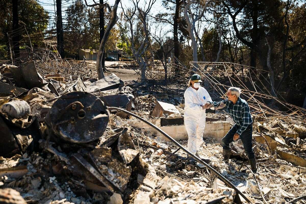 Dawn Hadjian helps her father, Richard Colbert, walk through the debris of his home in Napa, Calif. Saturday, October 14, 2017.