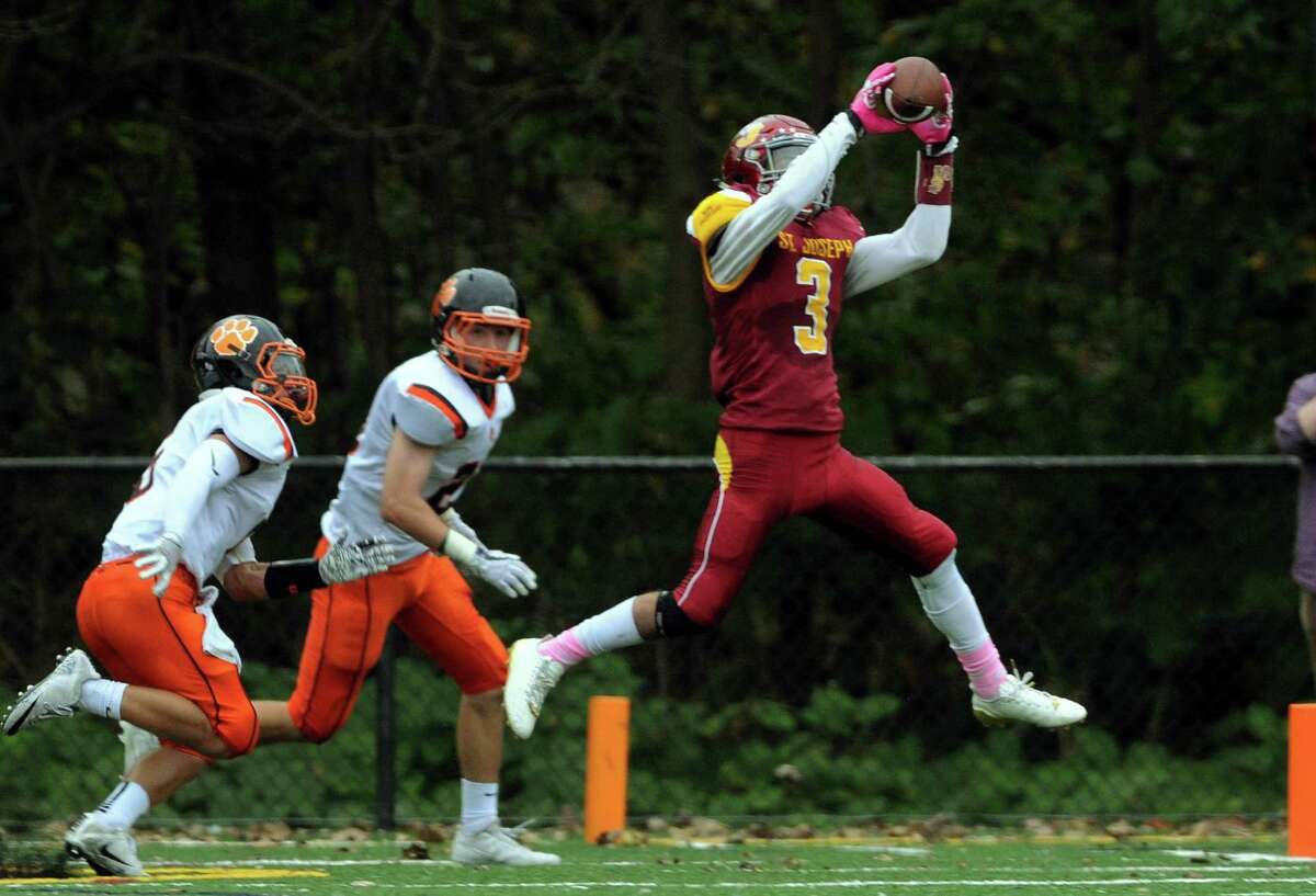 St. Joseph's Jared Mallozzi leaps up to complete a pass during football action against Ridgefield in Trumbull, Conn. on Saturday Oct. 14, 2017.