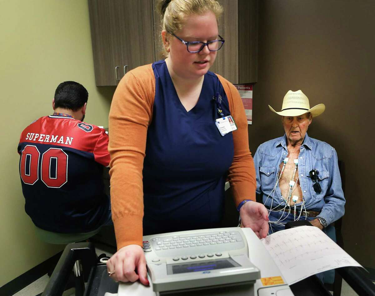 Miller (right) has an EKG administered by Hannah Muse, a Clinical Nurse Manager at South Texas Cardiology Institute in San Antonio. Meanwhile, Michael Garcia (left), a cardio tech, takes notes.