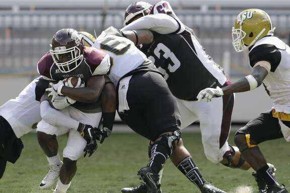 Texas Southern Tigers running back Brad Woodard (5) rushes between Alabama State Hornets defenders in the first quarter during the NCAA football game between the Alabama State Hornets and the Texas Southern Tigers at BBVA Compass Stadium in Houston, TX on Saturday, October 14, 2017.
