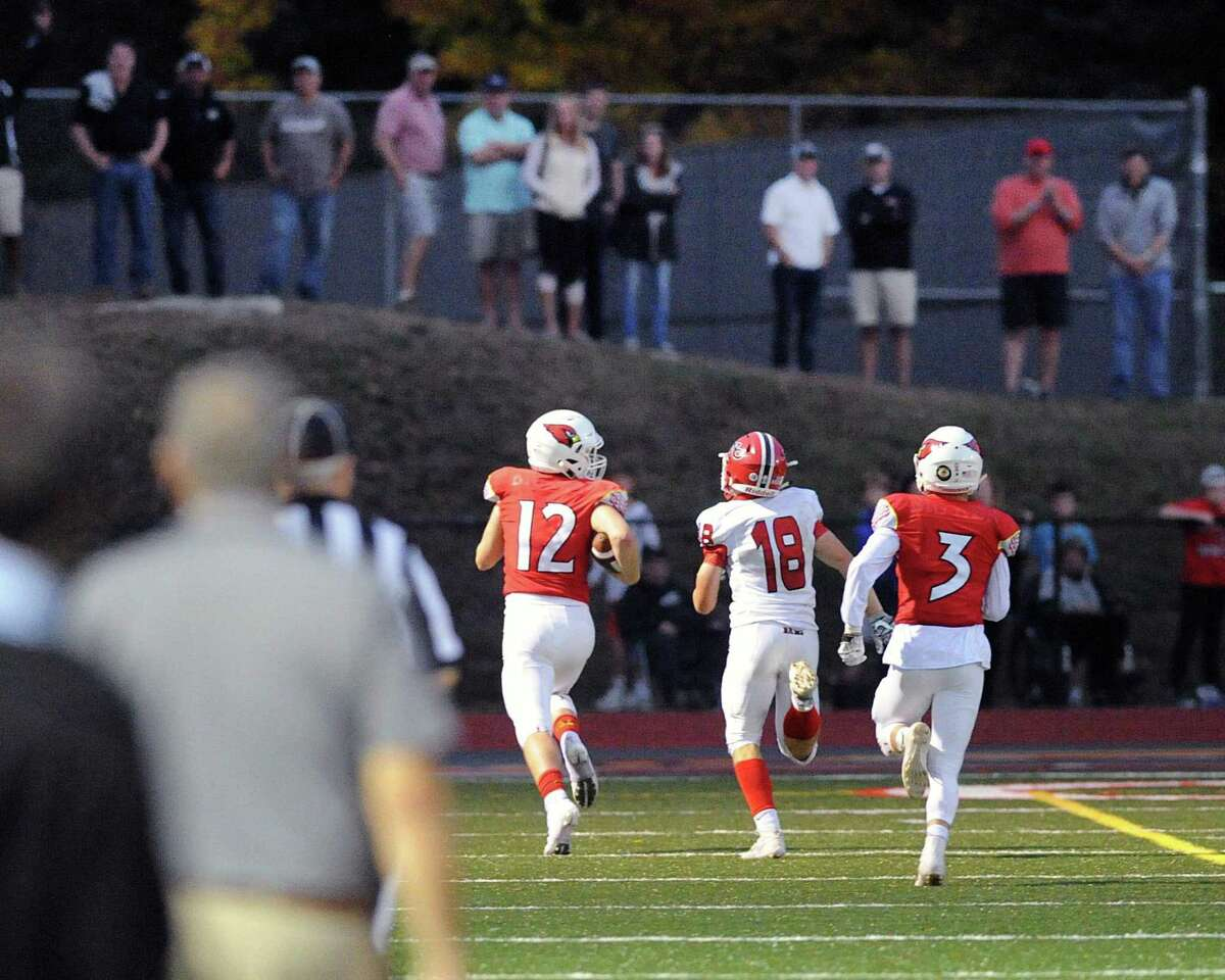 Greenwich quarterback Gavin Muir (12) looks over his shoulder as New Canaan defender Nico Savini (18) trails Muir en route to a 72-yard fourth-quarter touchdown run for Muir at Greenwich on Saturday. Greenwich defeated New Canaan 36-21.