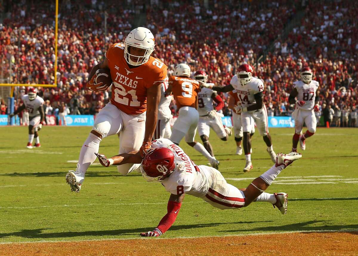 DALLAS, TX - OCTOBER 14: Kyle Porter #21 of the Texas Longhorns leaps past Kahlil Haughton #8 of the Oklahoma Sooners for a second quarter touchdown at Cotton Bowl on October 14, 2017 in Dallas, Texas. (Photo by Richard W. Rodriguez/Getty Images)