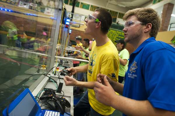Midland junior Stephen Gillman, center, and senior J.P. Zaremba, right, compete with their team during the FIRST Robotics Bot Bash Competition on Saturday, Oct. 14, 2017 at H. H. Dow High School. (Katy Kildee/kkildee@mdn.net)
