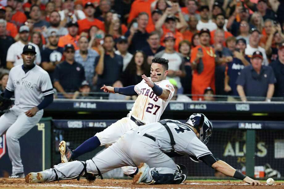 Jose Altuve slides around Yankees cathcer Gary Sanchez to score the winning run for the Astros in Game 2 on Saturday. Photo: Elsa /Getty Images / 2017 Getty Images