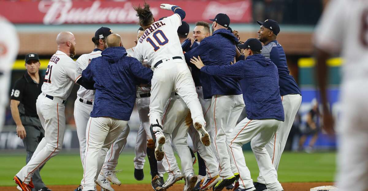 Houston Astros shortstop Carlos Correa (1) is mobbed by his teammates after hitting a double that allowed second baseman Jose Altuve (27) to score the winning run in the ninth inning of Game 2 of the ALCS at Minute Maid Park on Saturday, Oct. 14, 2017, in Houston. ( Brett Coomer / Houston Chronicle )