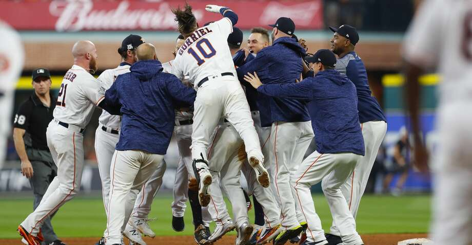 Houston Astros shortstop Carlos Correa (1) is mobbed by his teammates after hitting a double that allowed second baseman Jose Altuve (27) to score the winning run in the ninth inning of Game 2 of the ALCS at Minute Maid Park on Saturday, Oct. 14, 2017, in Houston. ( Brett Coomer / Houston Chronicle ) Photo: Brett Coomer/Houston Chronicle