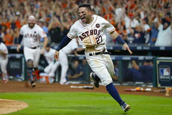 Houston Astros second baseman Jose Altuve (27) celebrates after safely sliding into home to give the Astros a 2-1 win over the New York Yankees after a double by shortstop Carlos Correa (1) in the ninth inning of Game 2 of the ALCS at Minute Maid Park on Saturday, Oct. 14, 2017, in Houston. ( Brett Coomer / Houston Chronicle )